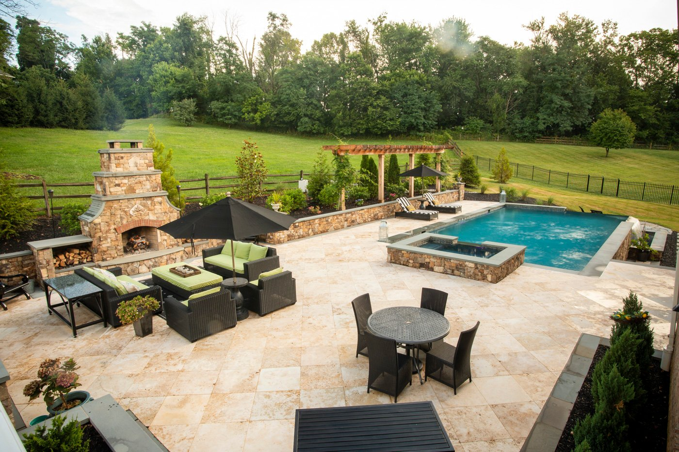 luxury patio with outdoor fireplace, spa, and pool