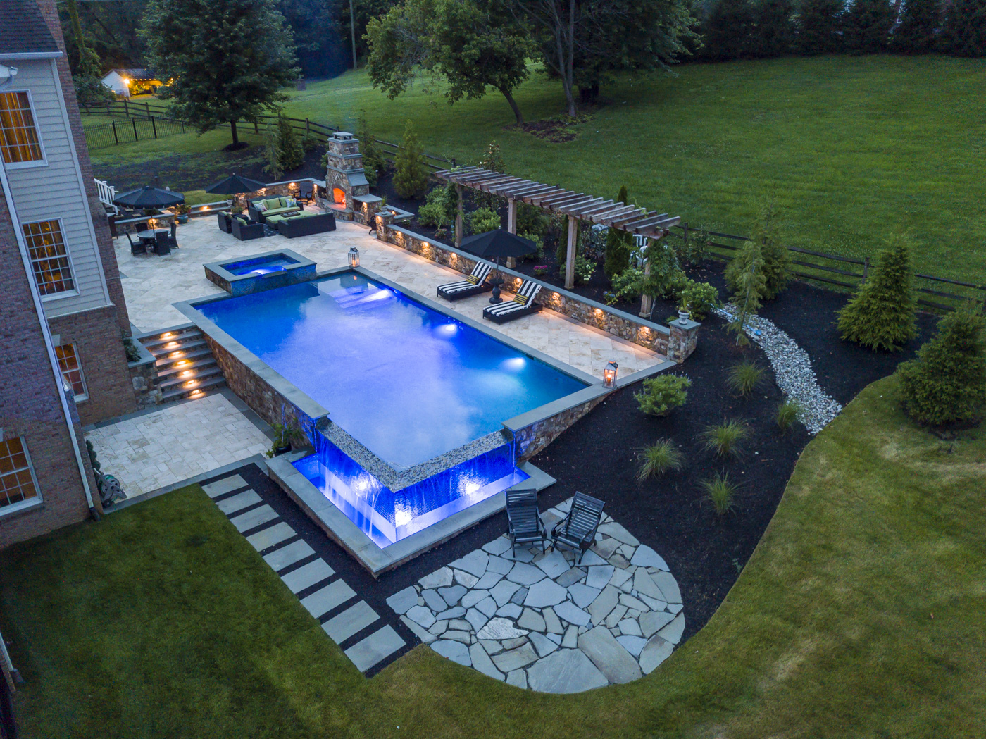 aerial view of infinity edge pool with 2 patios and outdoor fireplace