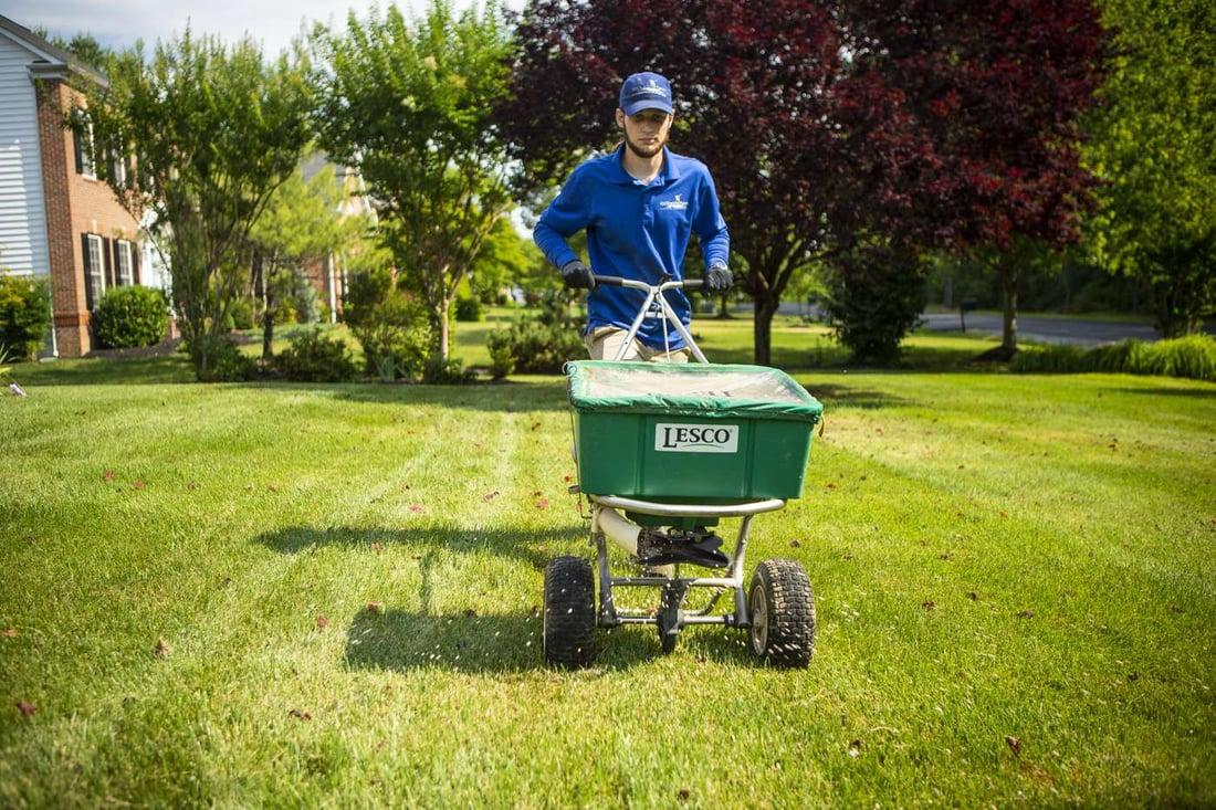 lawn technician applying fertilizer product