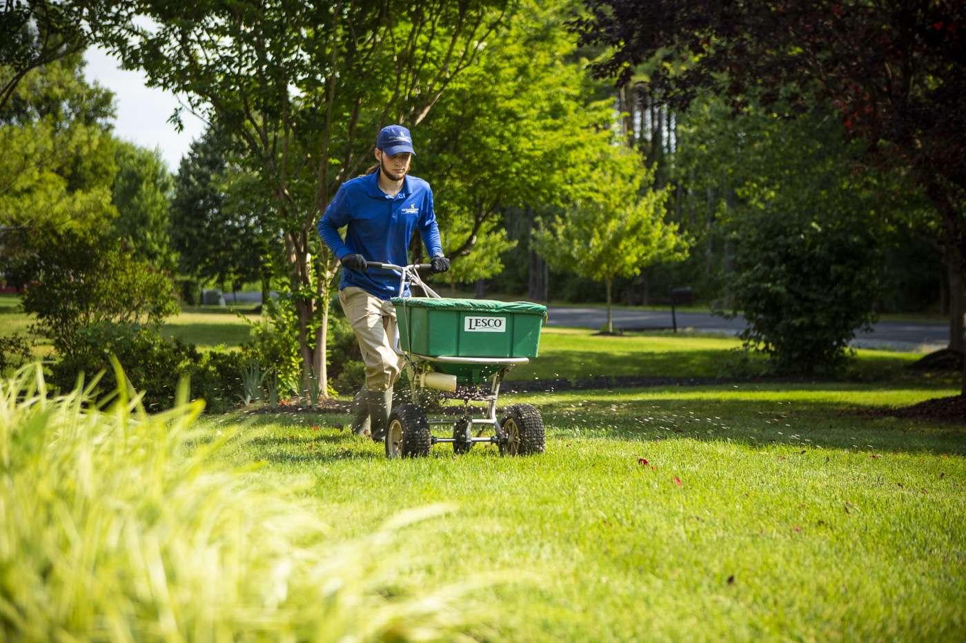 lawn technician fertilizing lawn
