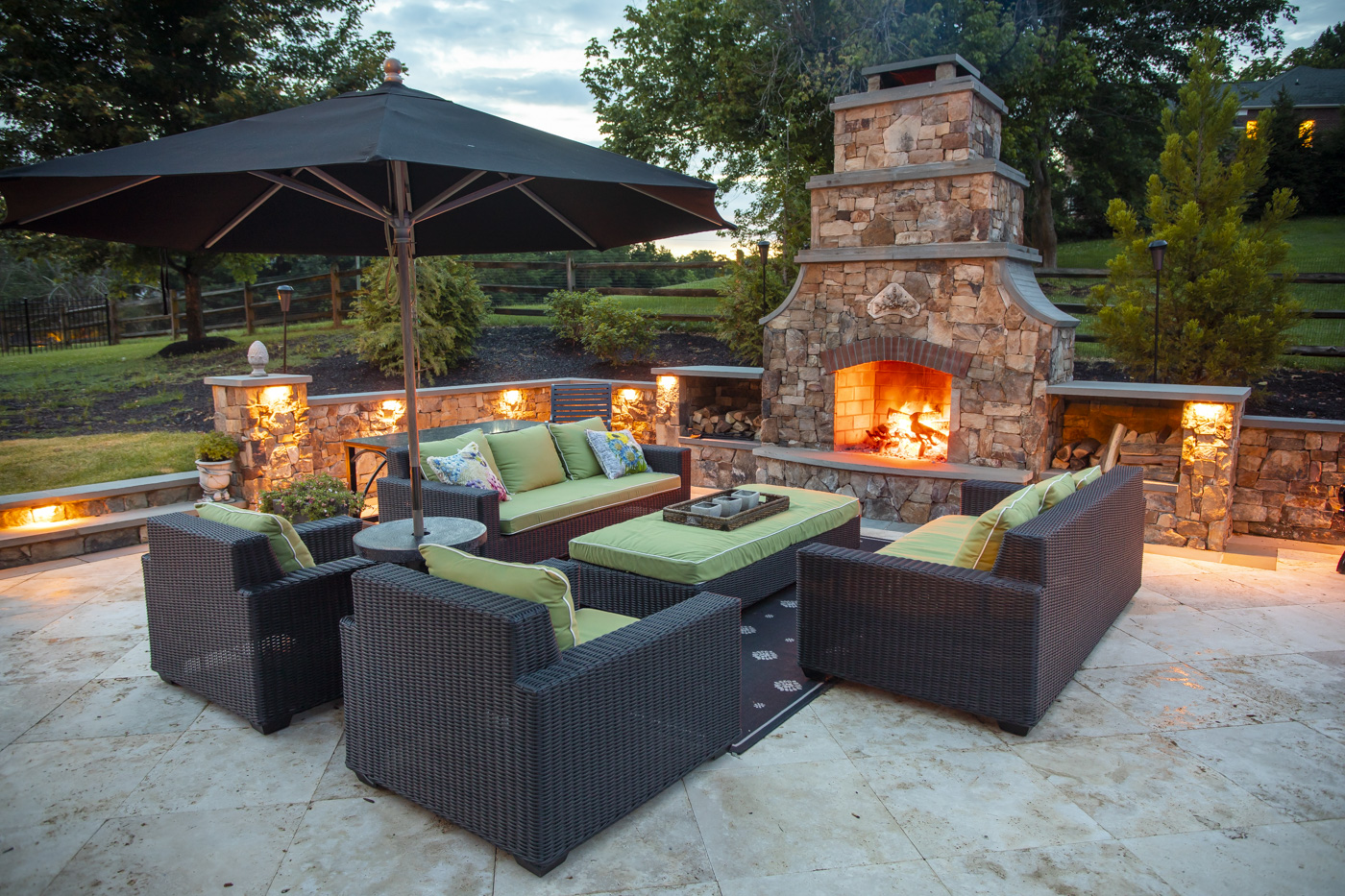 patio with outdoor fireplace and lighting designed by Rock Water Farm