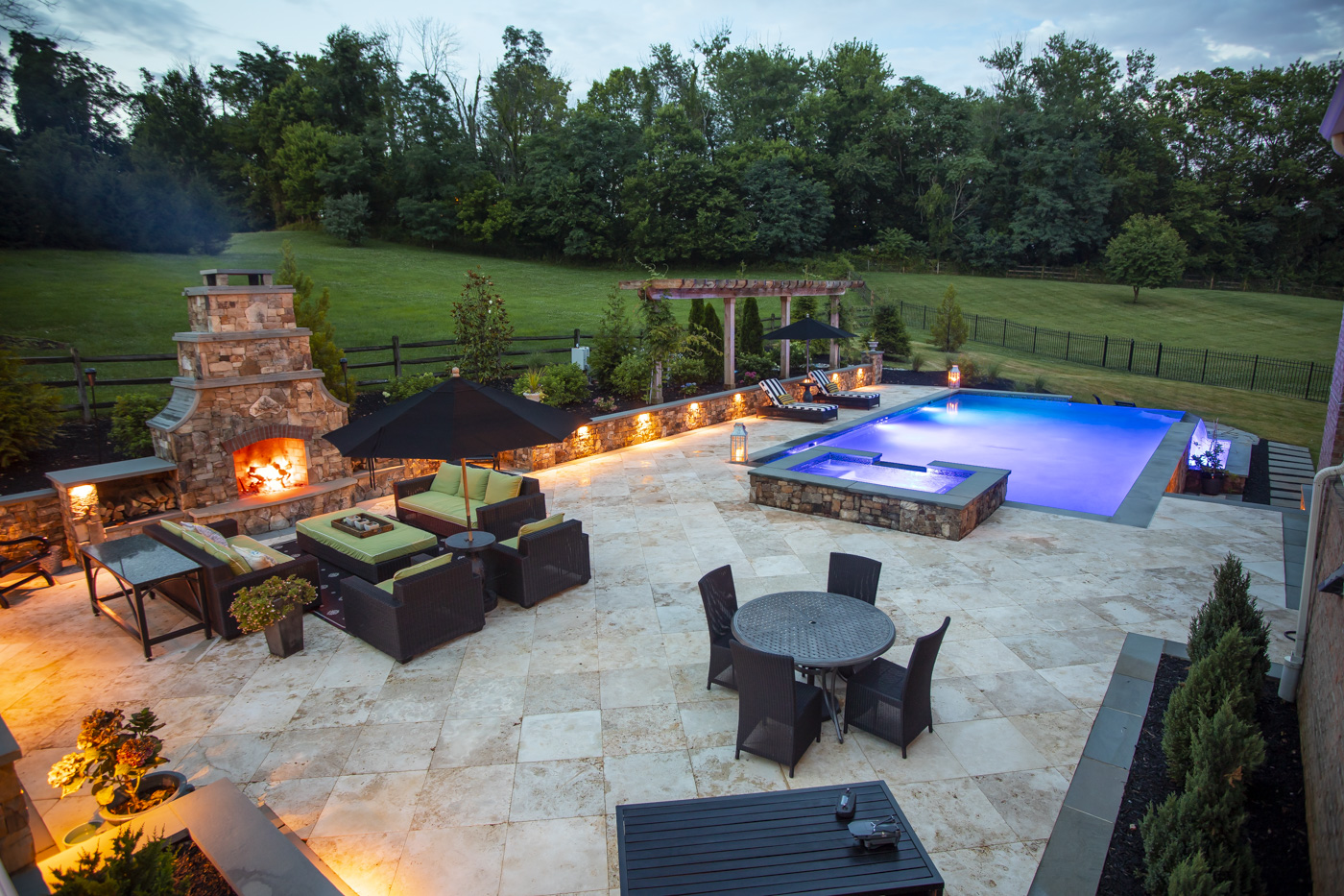 pool patio with natural stone, fire place, lighting, and hot tub