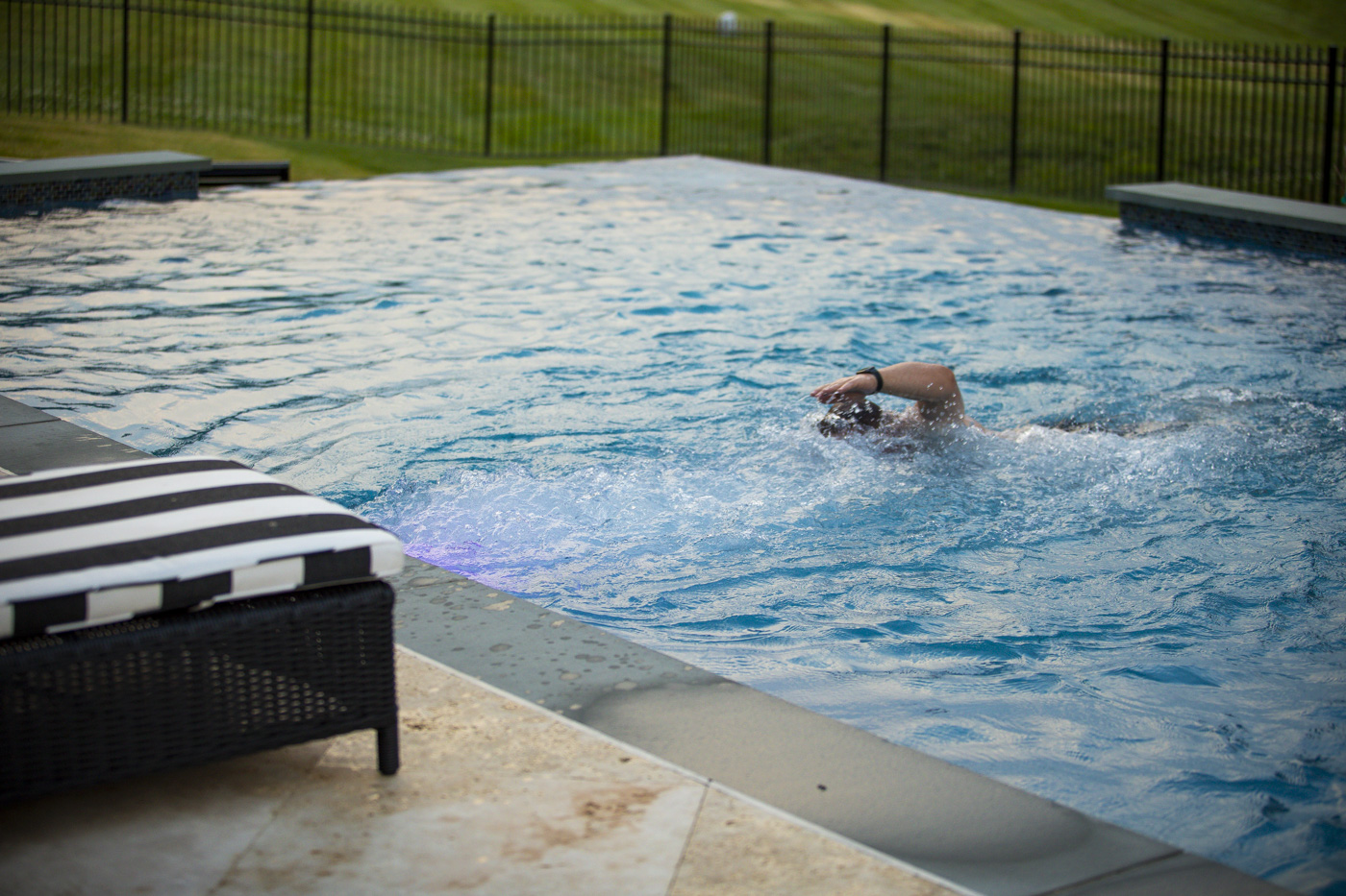 man swimming in pool with swim jets