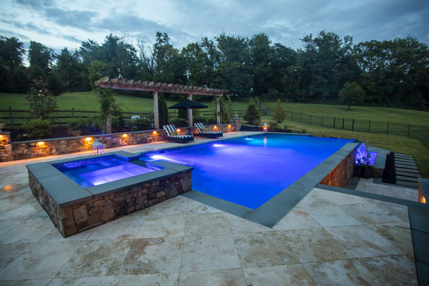patio with landscape lighting and pool lighting