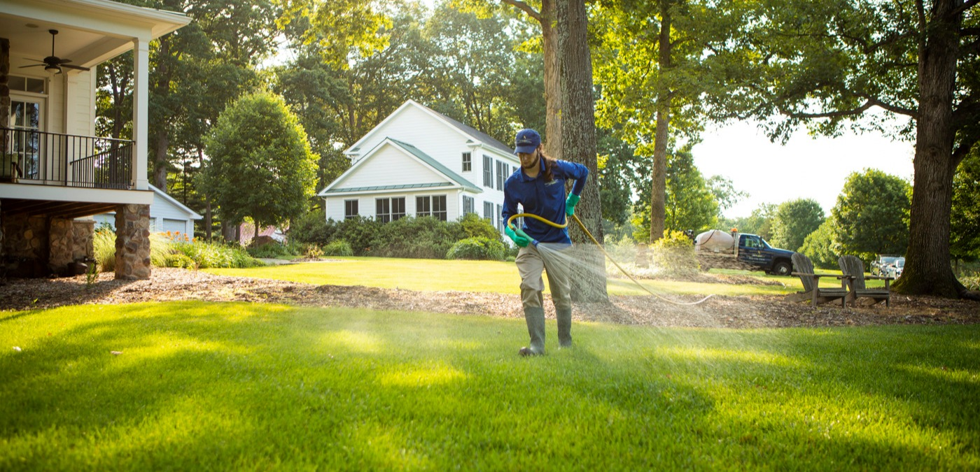 lawn care technician spraying to prevent weeds