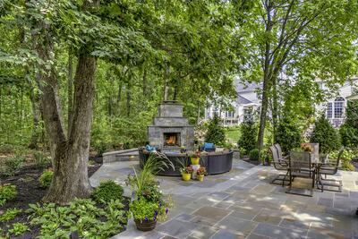 Private patio with fireplace and trees