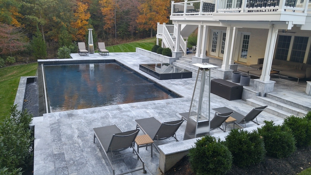 infinity pool with natural stone patio and hot tub