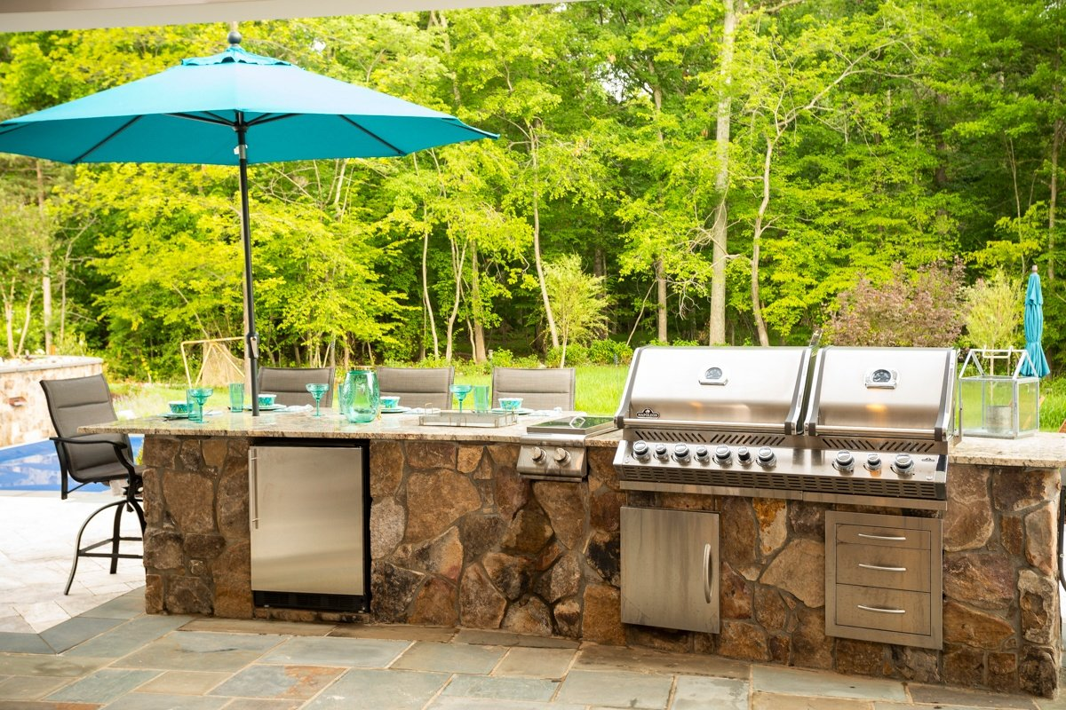 Full outdoor kitchen with appliances and seating