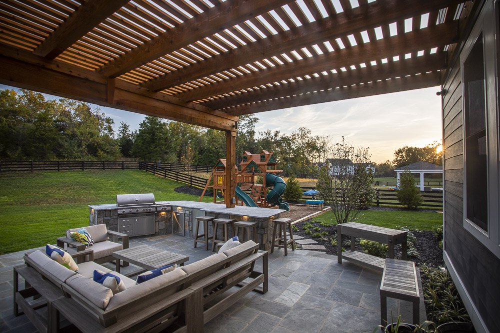 patio and outdoor kitchen under pergola designed by Rock Water Farm