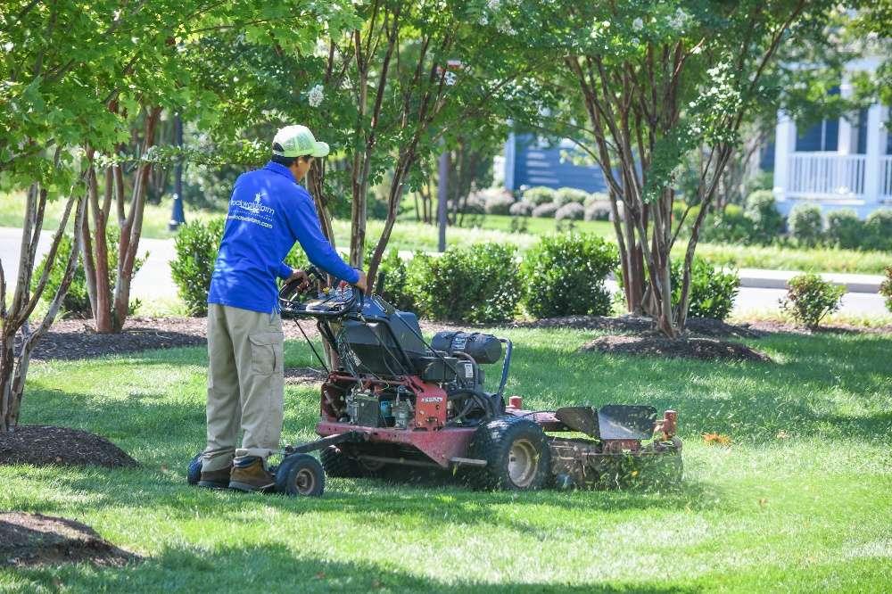 Lawn care technician mowing