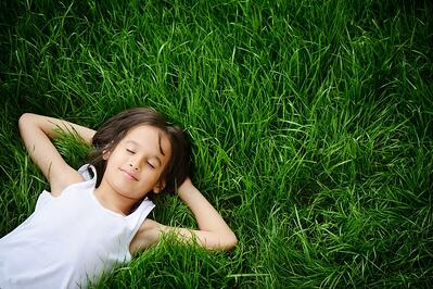 Happy child enjoying on grass field and dreaming.jpeg