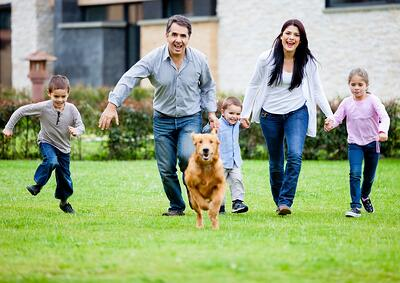 Family and dog in lawn with safe pest control