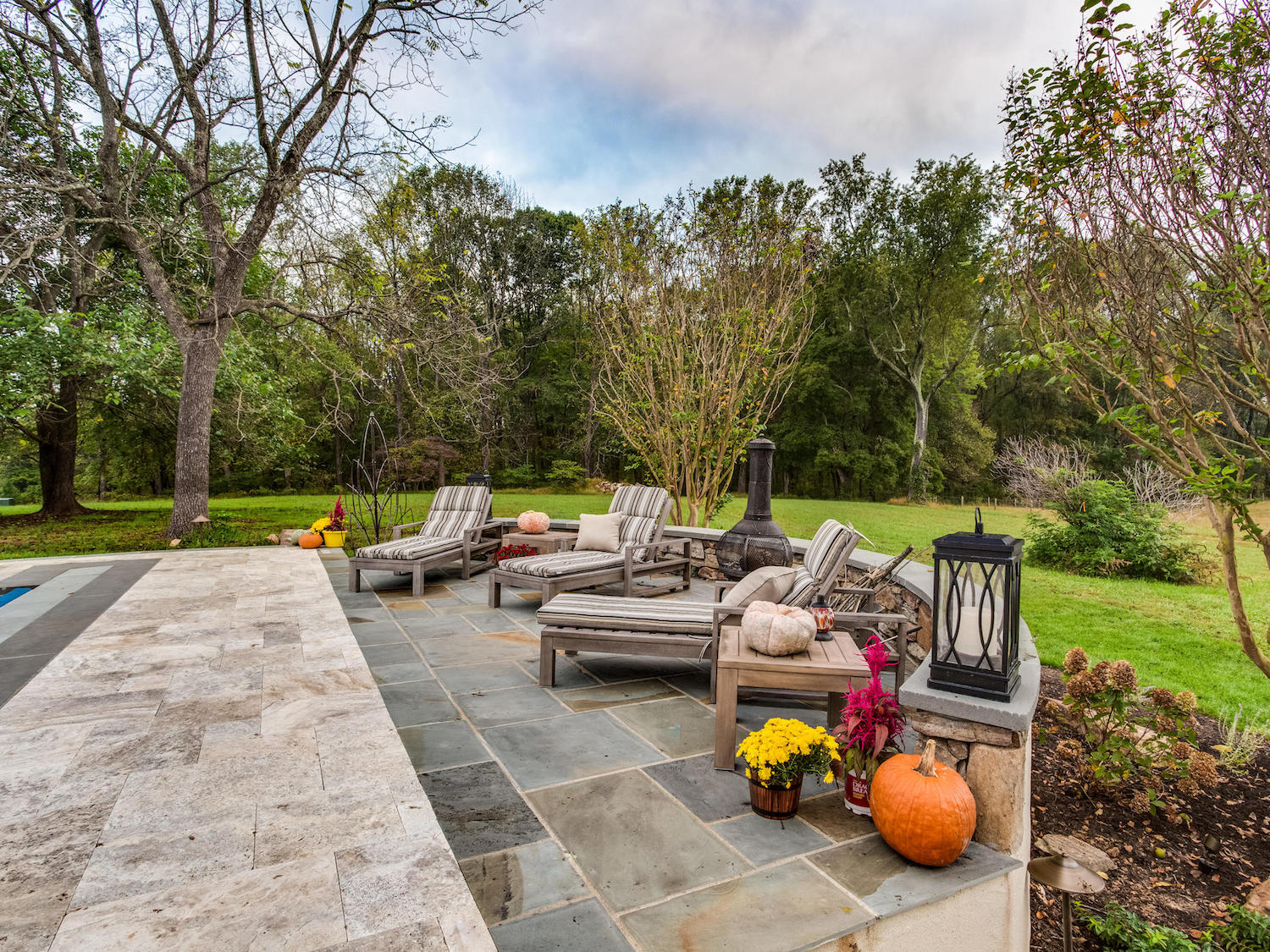 landscape patio with flagstone, plantings, and wall